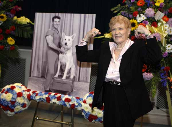 Elaine LaLannne strikes a characteristic pose near a portrait of her late husband Jack LaLanne at a memorial service for guru of physical fitness in Los Angeles Tuesday, Feb. 1, 2011. LaLanne died Jan. 23 at the age of 96. (AP Photo/Reed Saxon)